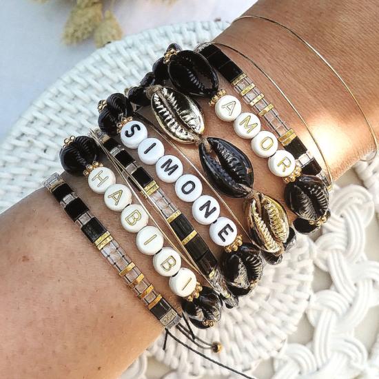 accumulation bracelets tendance mot ou prénom personnalisble coquillage cauri noir et or bracelets perles plates en verre japonaises